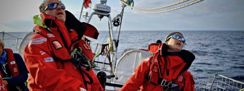 Two crew members on board Sanya Serenity Coast getting ready on coffee grinder