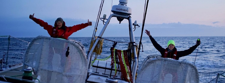 Jubilation as crew members on Sanya Serenity Coast hoist their arms aloft behind the helm stations as the near Race Finish