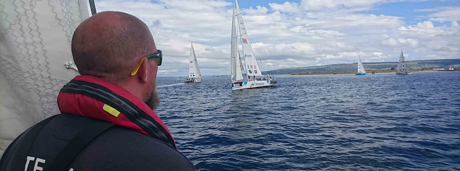 Dsre to Lead Crew Member looks out at competing yachts