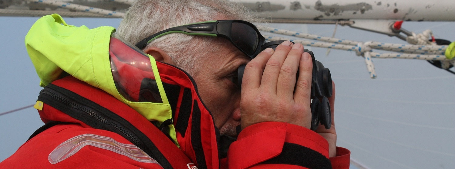 Crew member looking out through binoculars