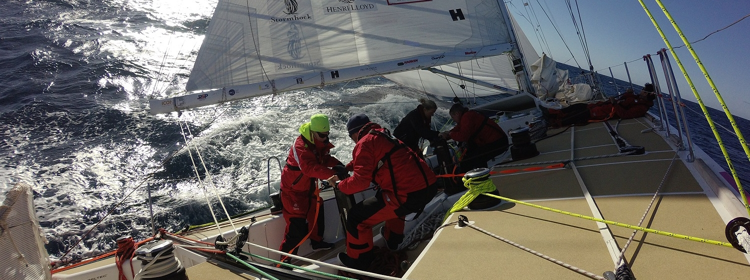Crew shown grinding sails on board during Race 11
