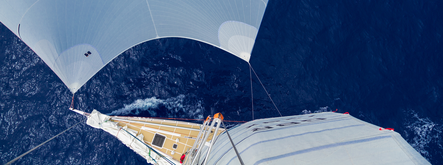 Looking down on a Clipper 70 at sea from the mast