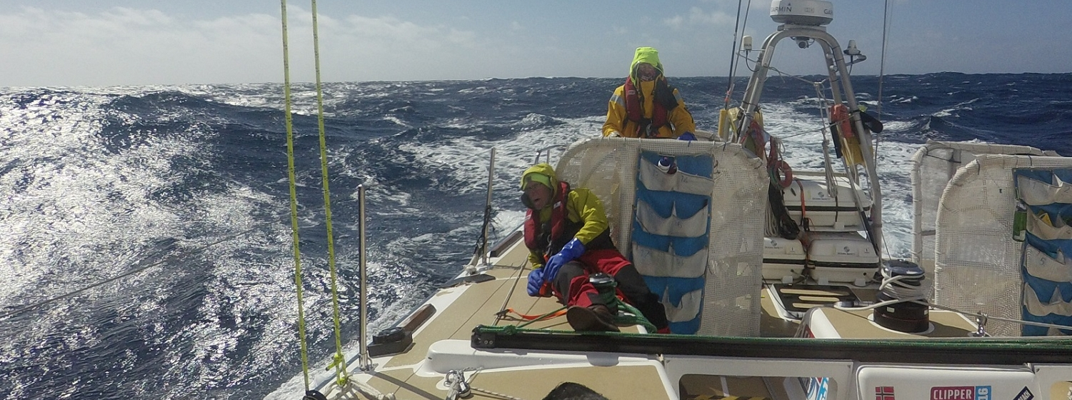 Crew shown helming in sunny, moderate conditions at sea