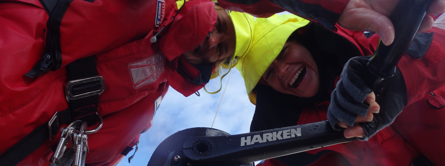Two crew members using a Harken grinder onboard during the last race