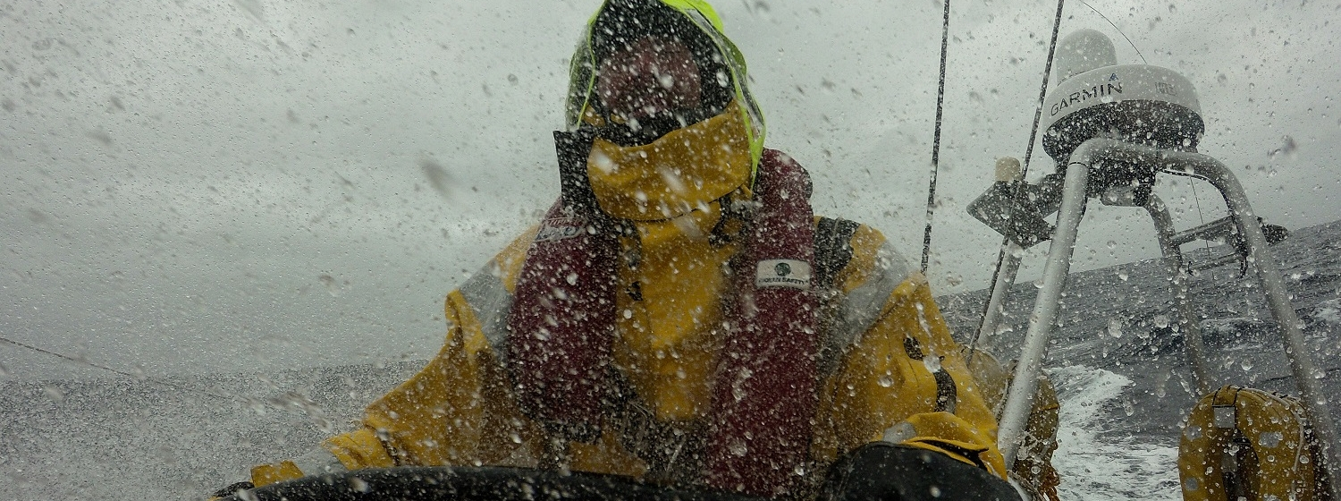 A crew member is pictured in wet conditions whilst helming