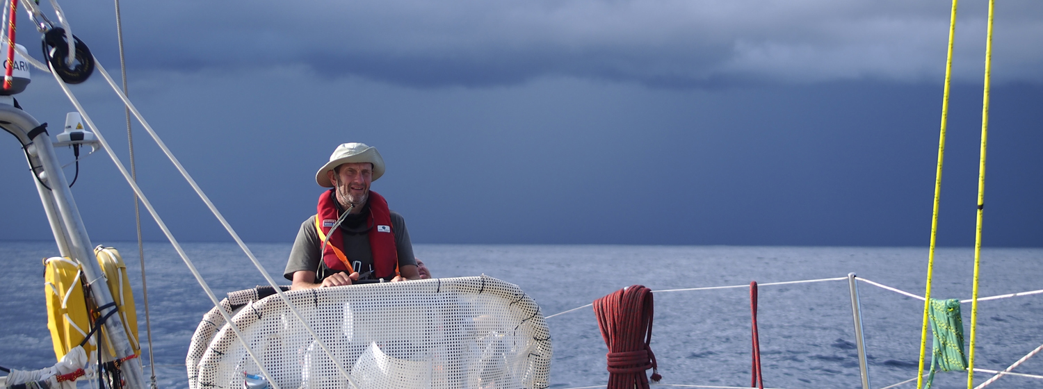 Dark sky overhead of a crew member helming at sea