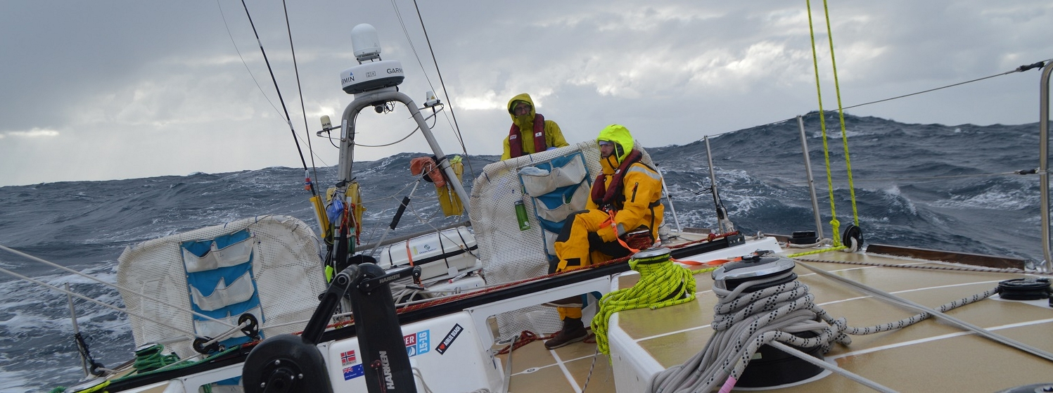 Crew shown helming on board Garmin heeled over with big following seas