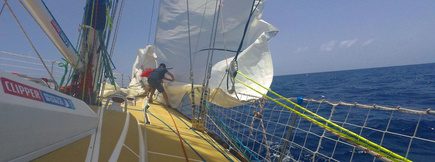 Two Nasdaq crew members pulling down the Staysail