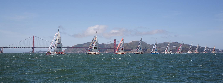 Clipper Race fleet parade of sail under Golden Gate Bridge in San Francisco