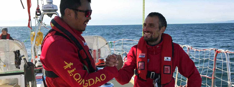 Qingdao Skipper Chris Kobusch celebrates with Ambassador Bobby Zhang