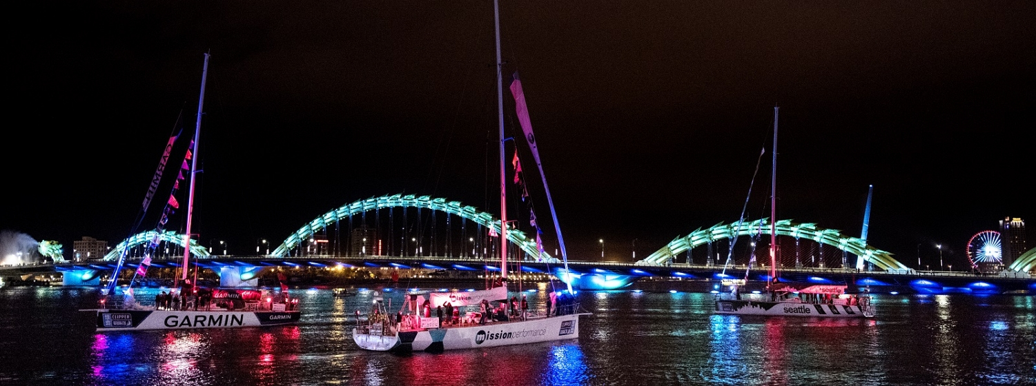 The Clipper Race fleet parades in front of the Dragon Bridge at night